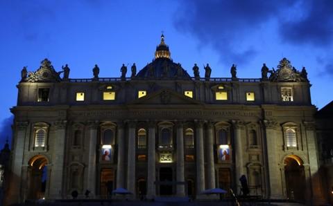 Tapeçarias com imagens de João Paulo II e João XXIII adornam a Basílica de São Pedro, no coração do Vaticano, onde será realizada a cerimônia de canonização dos papas | Stefano Rellandini/Reuters