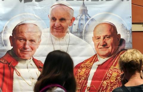 Mulher fotografa uma ilustração que reúne o papa Francisco e os dois beatos que serão santificados hoje, no Vaticano | Stefano Rellandini/Reuters