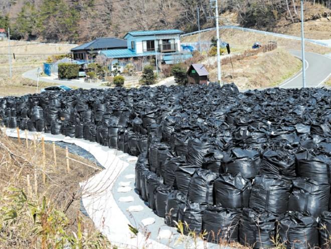 Sacos de resíduos contaminados por radiação são empilhados na estrada que leva a Miyakoji, que foi reaberta aos moradores | Ko Sasaki para The New York Times