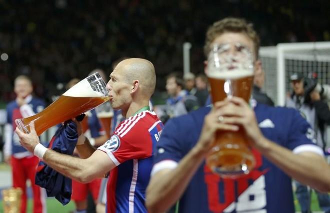 Robben (esq.) comemora a Copa da Alemanha seguindo a tradição cervejeira do país. Holandês é um dos craques que figuram na lista de convocados para a Copa | Reuters