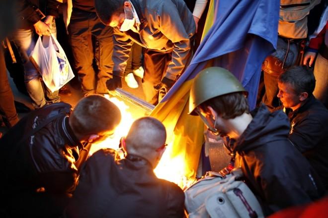 Manifestantes queimam bandeira da Ucrânia do lado de fora da prefeitura de Donetsk, no leste do país | Marko Djurica/ Reuters