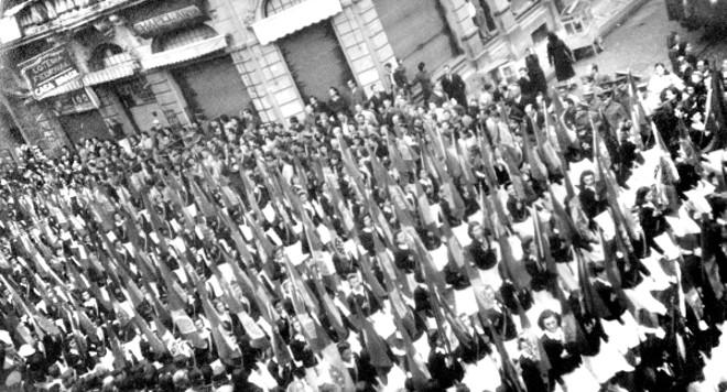 Desfile de alunas da Escola Normal portando bandeiras em profusão, na Rua Quinze de Novembro esquina com Dr. Murici. Uma imitação das apresentações executadas em eventos nos países totalitários europeus | Acervo Cid Destefani