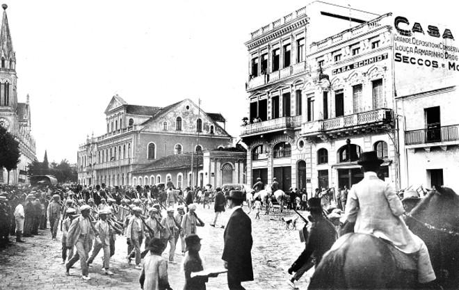 Alunos da Escola de Artífices de Curitiba desfilam pela Praça Tiradentes, em 21 de abril de 1913. Note-se a preocupação de mostrar a formação militar, cada criança leva ao ombro uma carabina de madeira | Acervo Cid Destefani