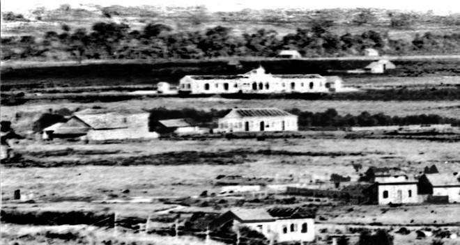 Detalhe de uma vista de Curitiba, feita em dezembro de 1883. Dois anos antes de ser inaugurada a Estação da Estrada de Ferro já aparece construída no meio do campo | Acervo Cid Destefani
