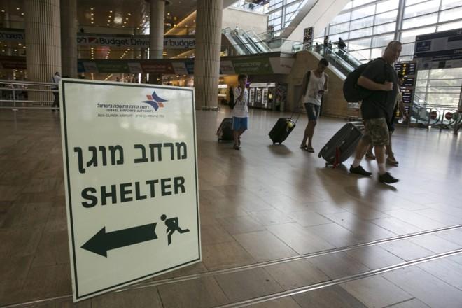 Passageiros passam por sinal no aeroporto de Ben Gurion, em Tel Aviv, indicando um abrigo antibombas: na última quinta-feira, os EUA suspenderam a proibição de voos com destino a Israel | Baz Ratner/Reuters