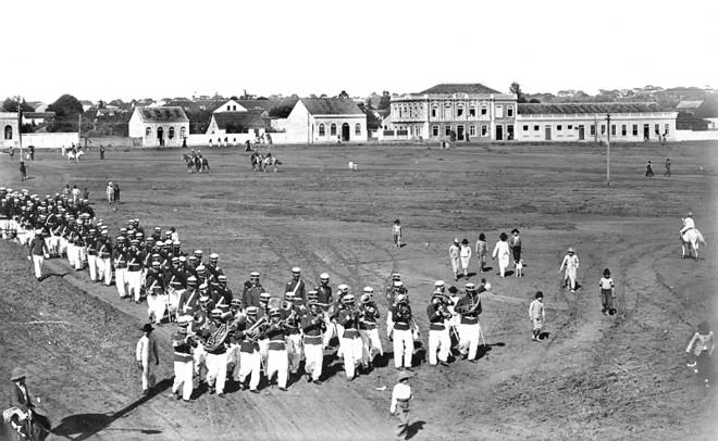 A Praça da Republica em 1906 um descampado usado para manobras militares do quartel que ali estava instalado, o 6º. Regimento de Artilharia, cujo efetivo vemos desfilando. O sobrado ao fundo era o Hospital Militar, mais tarde o prédio foi usado pelo Colégio Iguaçu | Acervo / Cid Destefani