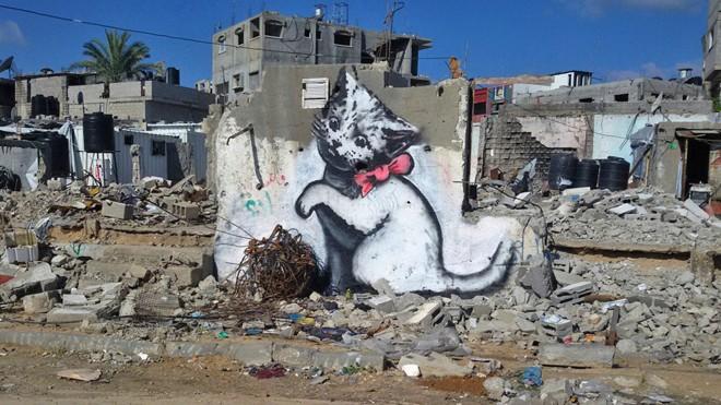 Arte de Banksy em muro parcialmente destruído de Gaza. | Divulgação/Reuters