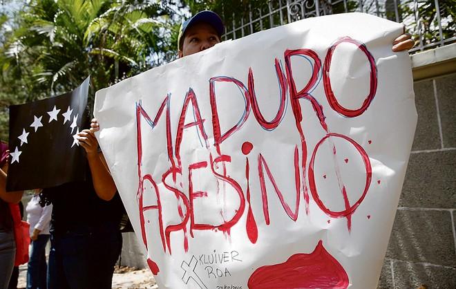 Jovem acusa Nicolás Maudro de assassino durante uma manisfestação em Caracas. | Carlos Garcia Rawlins/Reuters