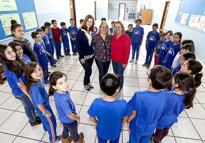A diretora Maria Cristina (ao centro) e equipe com alunos da Germano Paciornik: reunião com os pais criou pacto de trabalho conjunto. | Henry Milleo / Gazeta do Povo