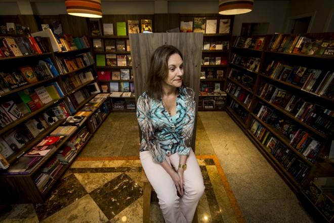 Luci Collin cercada de livros: a escritora garante que, ao longo de sua carreira, não mudou, mas a leitura sim. | Henry Milleo / Gazeta do Povo