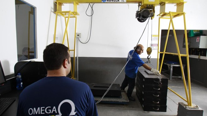 Funcionários da área de manutenção fazendo a calibragem de uma balança:receita de serviços ganhou importância. |