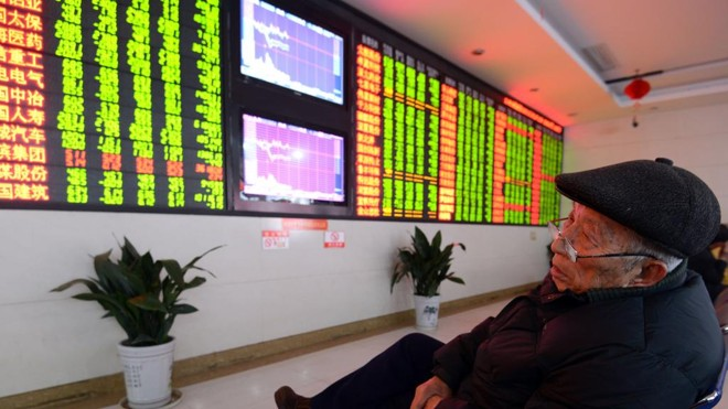 Investidor olha placar da bolsa chinesa. | STR/AFP