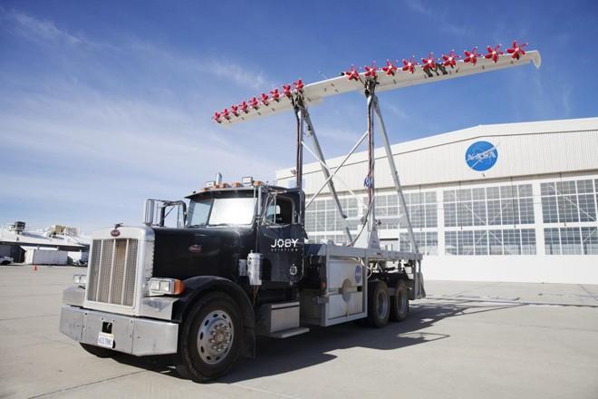 Caminhão leva um  protótipo do sistema pensado pela Nasa: uma asa de pouco mais de 9 metros, a mesma de um pequeno avião, equipada com 18 motores elétricos, cada um com uma pequena hélice vermelha. | EMILY BERL/NYT