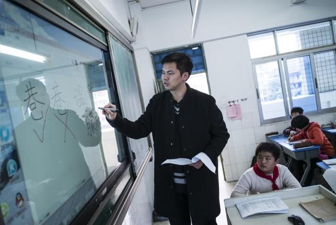 Lin Wei dá aula a alunos da sexta série em uma escola em Fuzhou, na China | LAM YIK FEI/NYT