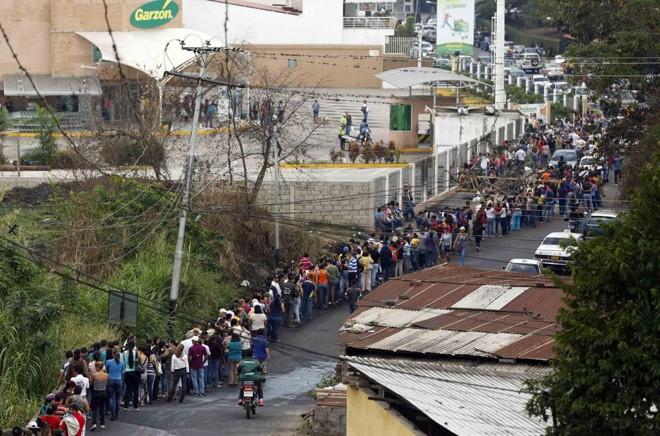 Pessoas formam fila, uma cena comum na Venezuela, para fazer as compras em um supermercado | JS/KR/Carlos Garcia Rawlins