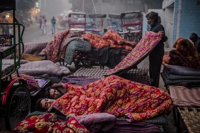 Homens dividem cobertor alugado por um mercador na cidade de Délhi, na Índia   DANIEL BEREHULAK/NYT