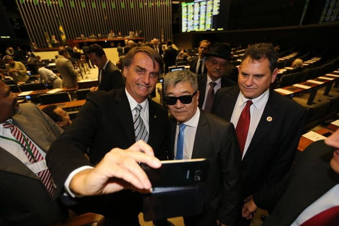 Jair Bolsonaro tira selfie com Newston Ishii, da Polícia Federal. | Alan Marques/Folhapress