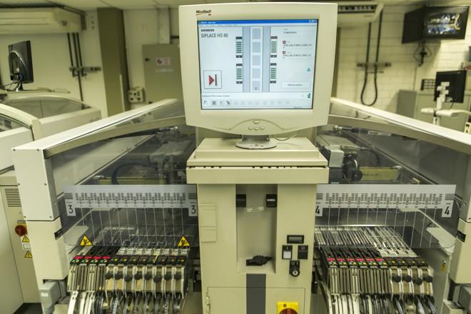 Máquinas compradas de empresas que encerraram atividades (como a Siemens Enterprise Communications, que deixou Curitiba em 2013) fazem a maior parte do trabalho na linha que produz as placas para as câmeras da Pumatronix. | (foto:Marcelo Andrade/Gazeta do Povo)