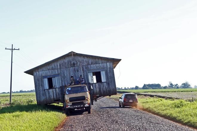 Carga inusitada: no Paraguai, casa é transportada em caminhão para outra região. Prática é comum no interior do país. | Albari Rosa/Gazeta do Povo