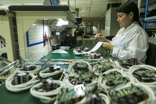 Os funcionários da linha de produção instalam, nas placas, itens mais pesados – como os capacitores, que armazenam energia para o disparo do flash da câmera. | (foto:Marcelo Andrade/Gazeta do Povo)