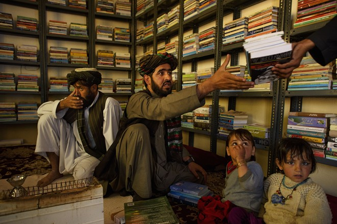 A iniciativa de criar bibliotecas em áreas afegãs em conflito é de Matiullah Wesa, na foto ao centro, com o irmão e as sobrinhas | Andrew  Quilty/NYT