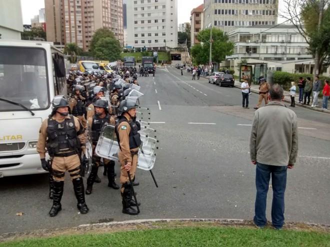 Um cordão de isolamento de policiais na rua Lysimaco Ferreira da Costa fez com que os manifestantes passassem ao Centro Cívico em conta-gotas. | Gazeta do Povo