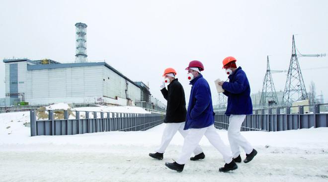 Visitantes caminham em frente ao quarto reator danificado da usina de Tchernóbil   Gleb Garanich/AP