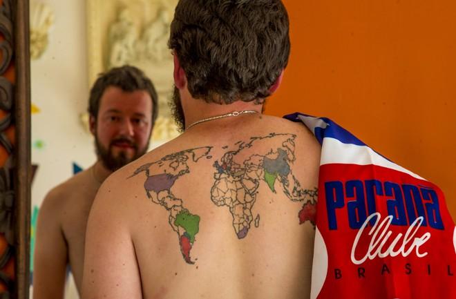 Guilherme com a bandeira do Paraná e o mapa mundial tatuado nas costas. A cada nova viagem, o paranista preenche o mapa. | Hugo Harada/Gazeta do Povo