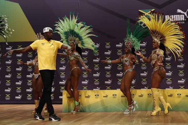 Bolt não se intimidou com a presença de passistas e se arriscou no samba | ADRIAN DENNIS/AFP