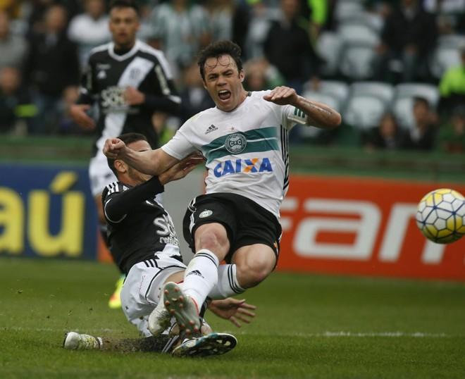 Mesmo acossado, Kléber bate na bola e marca o primeiro gol do Coritiba. | Lineu Filho/Gazeta do Povo
