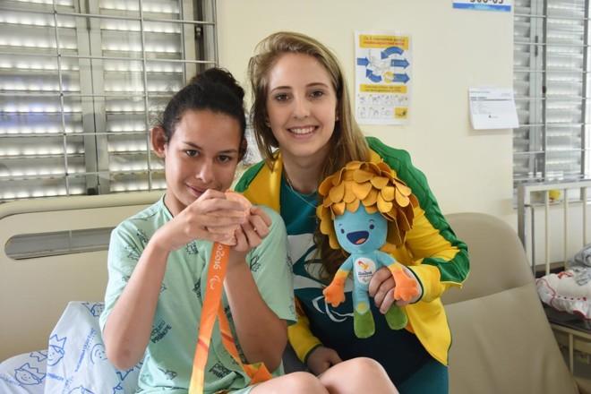 Danielle Rauen (dir.) e a paciente Renata Fernandes Batista, de 19 anos, durante visita da atleta ao Hospital Pequeno Príncipe. | Maria Fernanda Schneider /HPP