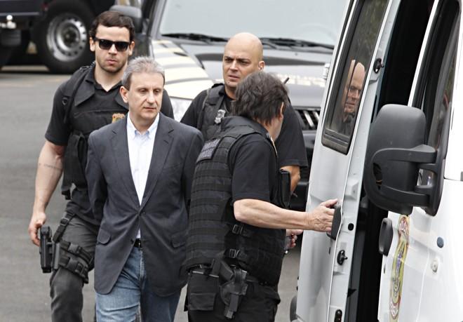 Youssef (de camisa branca) conduzido por policiais federais para um depoimento: ajuda nas investigações rendeu pena bem menor ao doleiro. | Aniele Nascimento/Gazeta do Povo