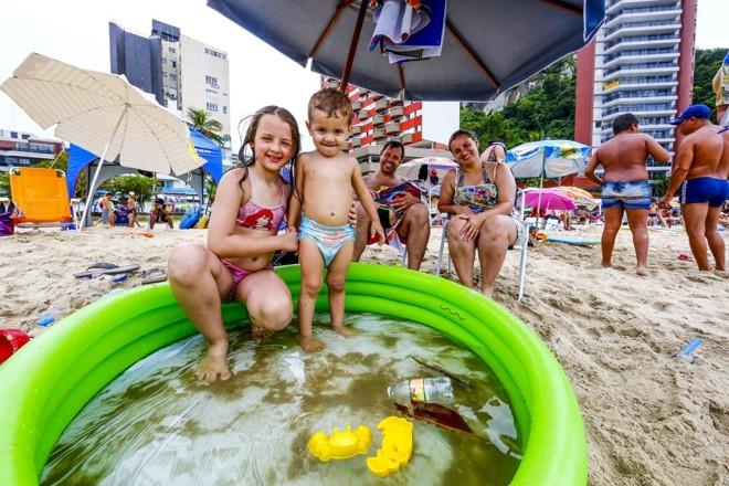 Fábio e Kamylla Moura assistem aos filhos se refrescando na piscininha montada na areia | Lineu Filho/Tribuna do Paraná