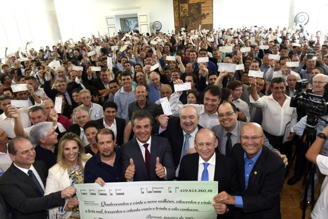 Richa e prefeitos posam para foto com o cheque repassado aos municípios pelo governo do estado | Ricardo Almeida / ANPr