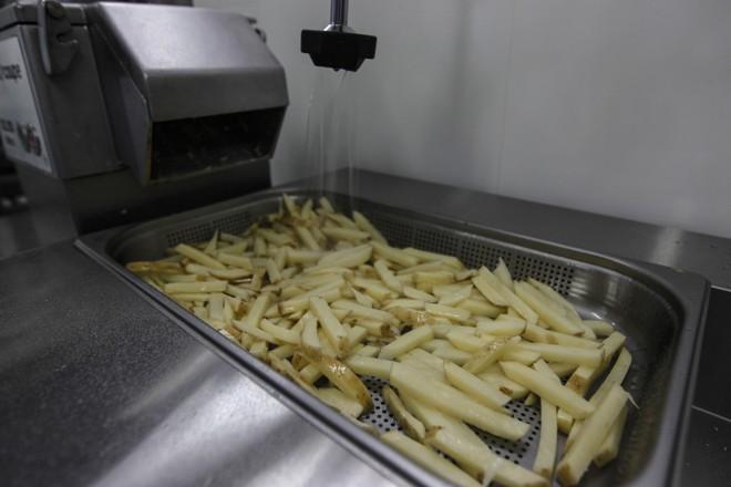"""Atualmente, até pela intenção de manter um comércio local, somente uma pequena parte da produção vai para a pré-fritura. Mais uma vez, as batatas são lavadas, para retirar o excesso de amido. É a famosa """"água de batata"""". Depois, são aquecidas, para eliminar as enzimas que escurecem o produto. Só então, vão para a frigideira.   Jonathan Campos/Gazeta do Povo"""