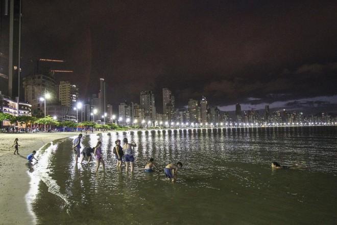 Família na praia, à noite, em Balneário Camboriú | Daniel Castellano/GAZETA