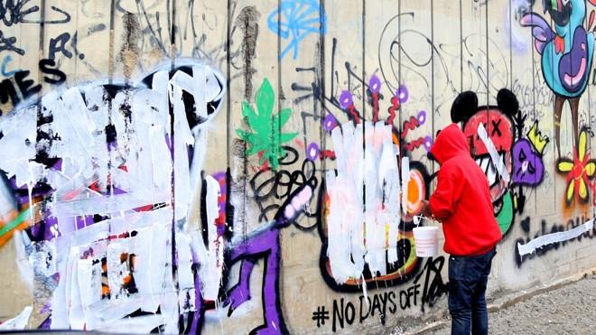Funcionário apaga pichação feita por Justin Bieber no muro de hotel em São Conrado, no Rio de Janeiro, em 2013 | Xande Nolasco/Estadão Conteúdo