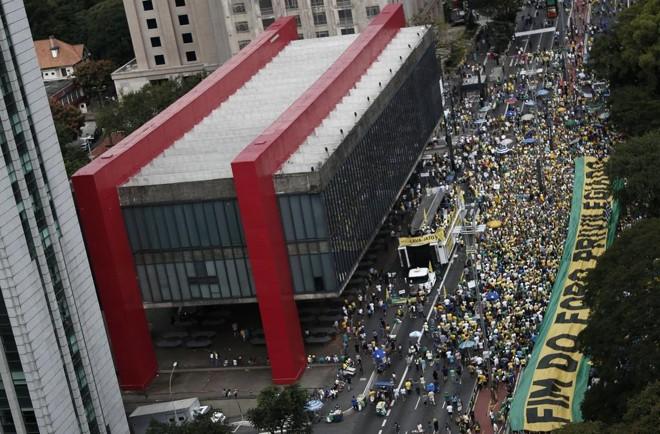 Manifestantes estendem uma bandeira pelo fim do foro privilegiado na Avenida Paulista, em São Paulo | MIGUEL SCHINCARIOL/AFP