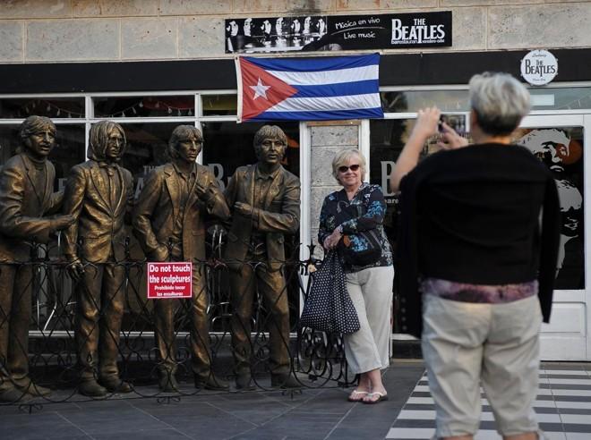 Turista posa ao lado de esculturas dos Beatles em frente de bar temático em Varadero, província de Matanza. | Yamil Lage/AFP