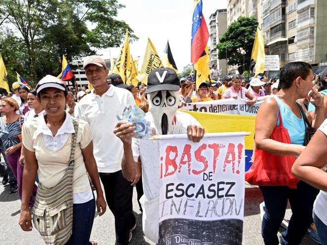 Manifestante leva cartaz pedindo o fim da escassez e da inflação | Juan Barreto/AFP