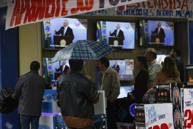 População assiste ao pronunciamento de Temer em loja na rua Marechal Deodoro, no Centro de Curitiba | Átila Alberti/Tribuna doParaná /