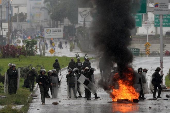 Polícia avança contra manifestantes da oposição bloqueando uma avenida durante um protesto anti-governo, em Caracas | FEDERICO PARRAAFP