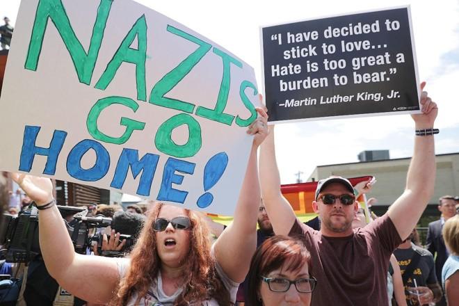 Manifestantes gritam insultos e fazem barulho na tentativa de abafar coletiva de imprensa realizada pelo blogueiro alt-right Jason Kessler, no dia 13 de agosto de 2017, em Charlottesville, Virgínia. Kessler, que ajudou a organizar a reunião do Unite the Right um dia antes, responsabilizou as autoridades de Charlottesville e a polícia por não terem protegido os direitos da primeira emenda dos participantes da manifestação: supremacistas brancos, neonazistas, membros Ku Klux Klan e alt-right | CHIP SOMODEVILLA/AFP