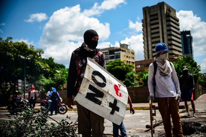 Ativistas anti-governo de Maduro protestam nas ruas de Caracas, na Venezuela | RONALDO SCHEMIDT/ AFP
