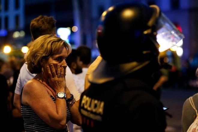 Uma mulher gesticula enquanto é escoltada por policiais para fora de uma área isolada depois que uma van passou por cima de uma multidão, matando 13 pessoas e ferindo mais de 80 em Rambla, Barcelona, rua mais popular da cidade | PAU BARRENA/AFP