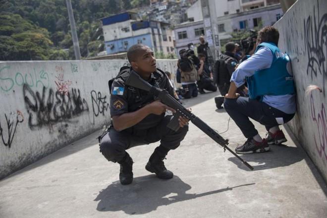 Polícias e jornalistas se protegem durante operação para combater traficantes de drogas fortemente armados na favela da Rocinha, no Rio de Janeiro, em 22 de setembro de 2017. | MAURO PIMENTEL/ AFP