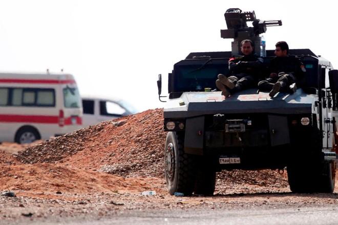 Membros das forças de segurança do Egito descansam no deserto depois do conflito deste sábado (21) | MOHAMED EL-SHAHEDAFP