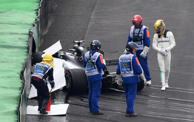Lewis Hamilton observa o carro destruído após sair na curva e bater contra a proteção de pneus no treino classificatório. | Nelson Almeida/AFP