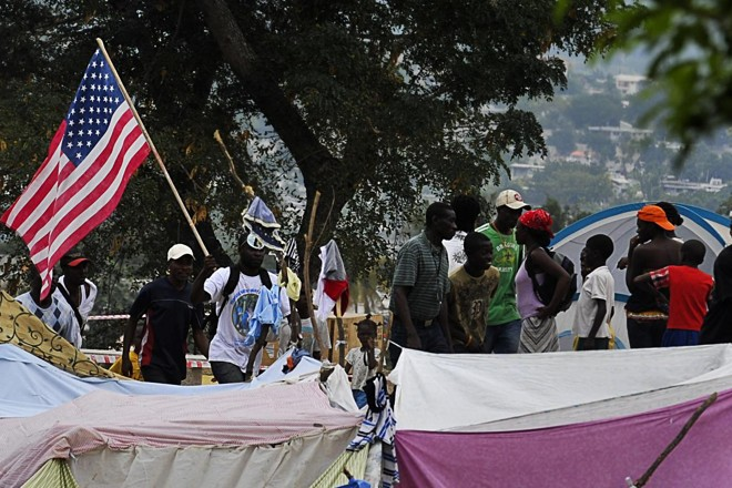 Haitianos carregam bandeira norte-americana no meio de um campo de refugiados, em Porto Príncipe, após o terremoto de 2010 | LA/dec/ LUIS ACOSTA