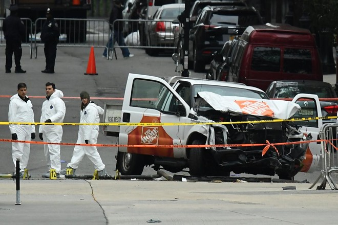 Investigadores trabalham em torno dos destroços da caminhonete do Home Depot utilizada no ataque terrorista em Nova York no dia 31 de outubro de 2017 | JEWEL SAMAD/AFP